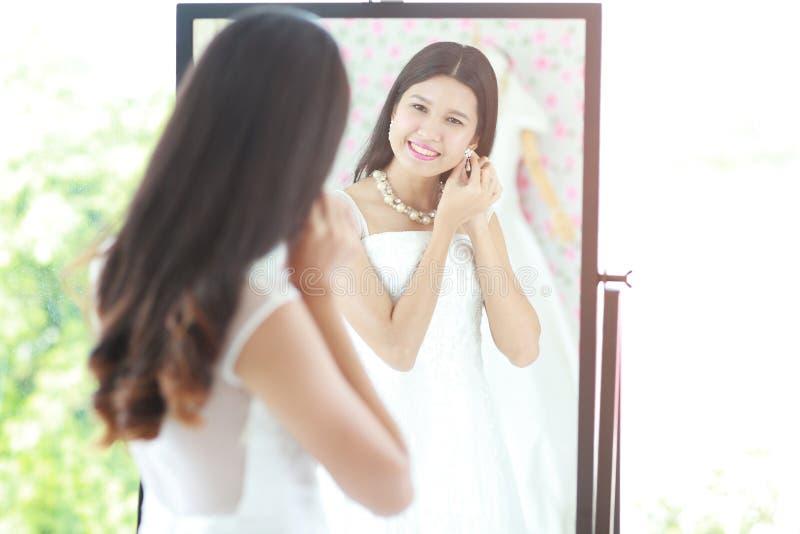 Le portrait de la belle jeune mariée asiatique a mis dessus la boucle d'oreille regardant dans le mirr photos stock