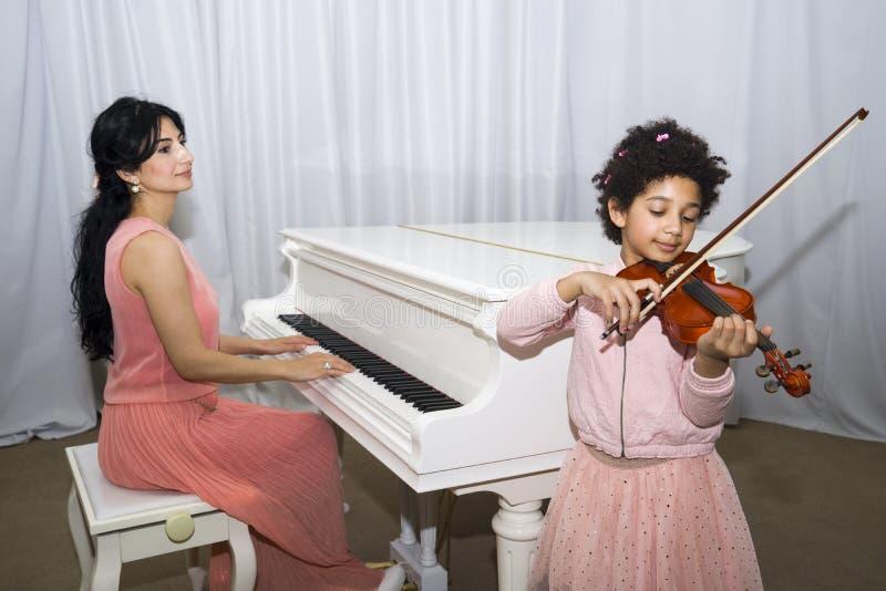 Le portrait de la belle obscurité heureuse a pelé la petite fille à l'aide d'un violon tout en jouant une mélodie image libre de droits