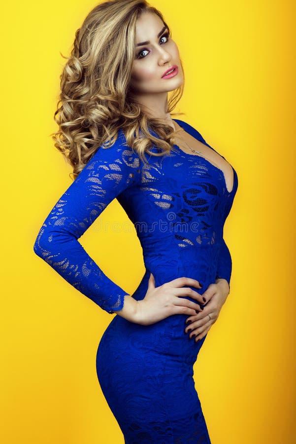 Le portrait de la dame sexy magnifique avec de longs cheveux ondulés luxuriants portant le bleu transparent serré-a adapté la rob image stock