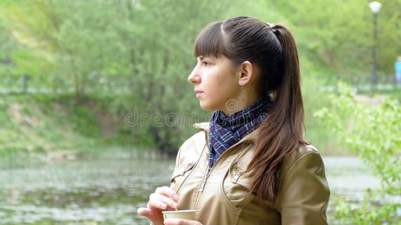 Le portrait de la femme attirante regarde pensivement au-dessus de la rivière a photo libre de droits