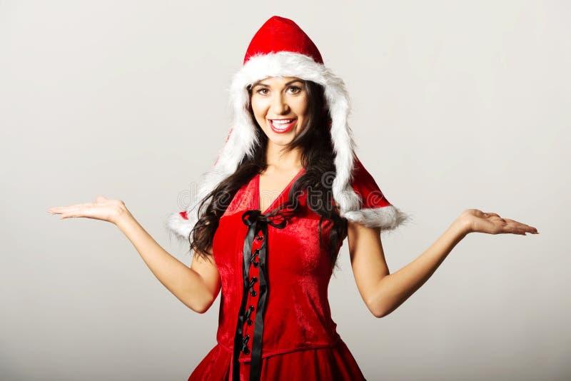 Le portrait de la femme avec le geste de mains ouvert portant Santa vêtx image libre de droits