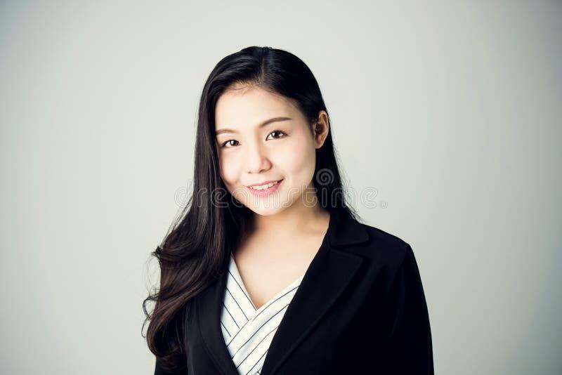Le portrait de la femme d'affaires dans un costume est souriant et regardant en avant Sur un fond blanc photo stock