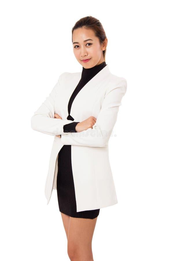 Le portrait de la femme de sourire d'affaires se tient et bras croisé images stock