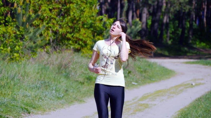 Le portrait de la femme fatiguée d'athlète se reposant, se ferment  image stock