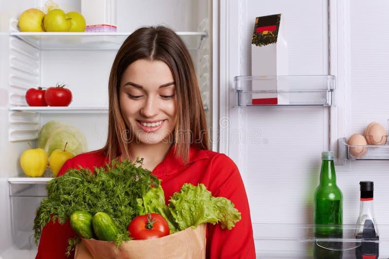 Le portrait de la femme heureuse avec l'expression gaie tient le sac de papier avec des tomates, cucmbers, aneth et la laitue, vi photo libre de droits
