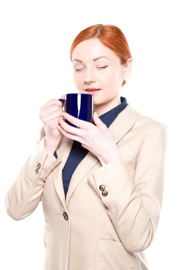 Le portrait de la femme heureuse d'affaires a inhalé l'odeur de café, d'isolement photographie stock libre de droits