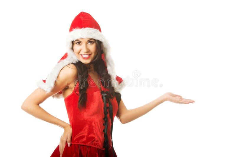 Le portrait de la femme jugeant quelque chose invisible dans la main droite portant Santa vêtx photos libres de droits