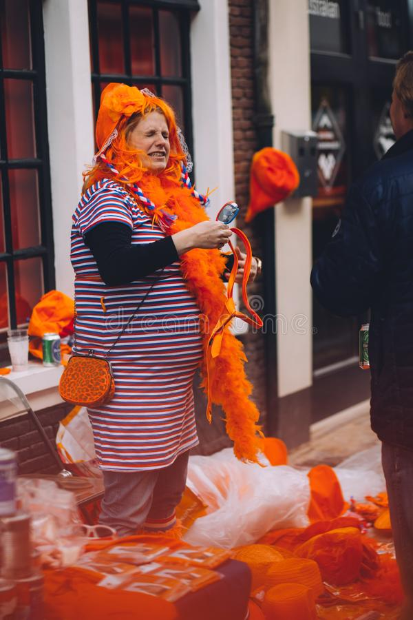 Le portrait de la femme s'est habillé dans le chapeau orange et fou, vendant l'ordure sur la festivité de jour du ` s de roi photo stock