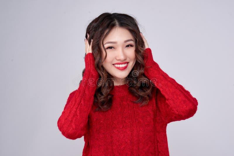 Le portrait de la fille asiatique d'hiver de beauté en rouge a tricoté la robe de laine Vacances de Noël photographie stock libre de droits
