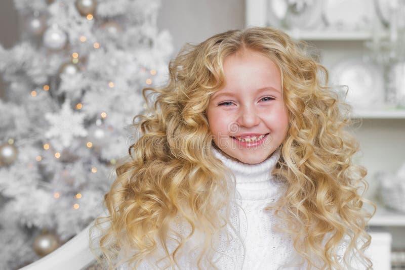 Le portrait de la fille assez petite très de sourire de blonde dans Noël a décoré le studio photographie stock