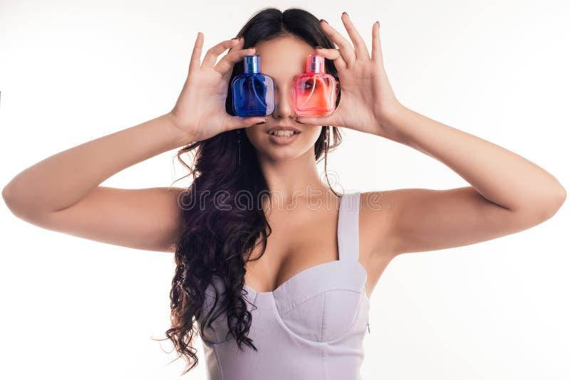 Le portrait de la fille attirante ferme ses yeux avec des bouteilles de parfum photographie stock