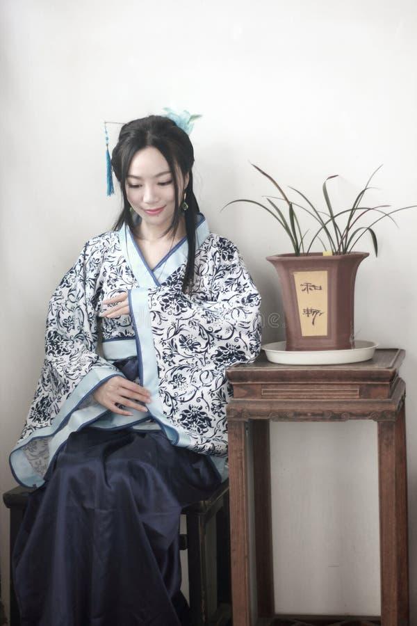 Le portrait de la fille chinoise asiatique dans la robe traditionnelle, portent le style bleu et blanc Hanfu, se reposer de porce photographie stock