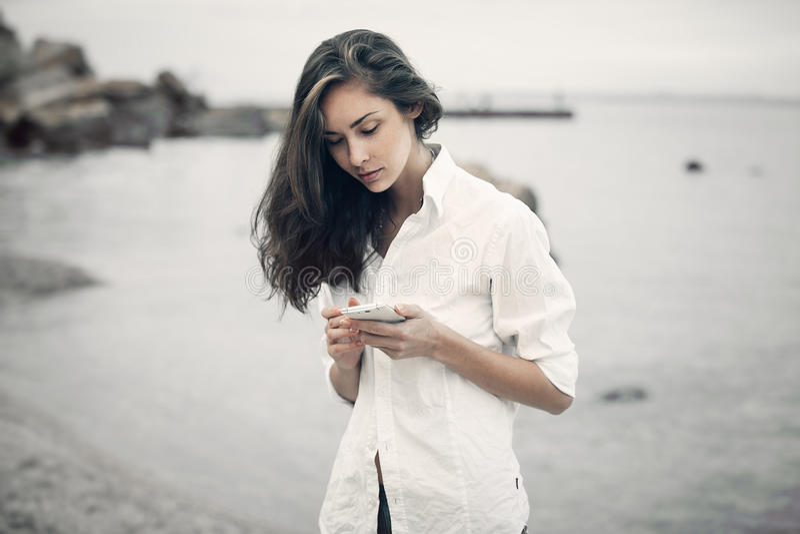 Le portrait de la fille d'adolescent marchant sur la plage vérifie en ligne le téléphone portable attendant un message image stock