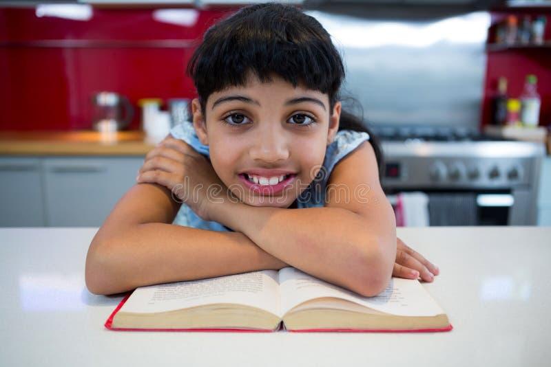 Le portrait de la fille de sourire avec des bras a croisé au-dessus du roman dans la cuisine image stock