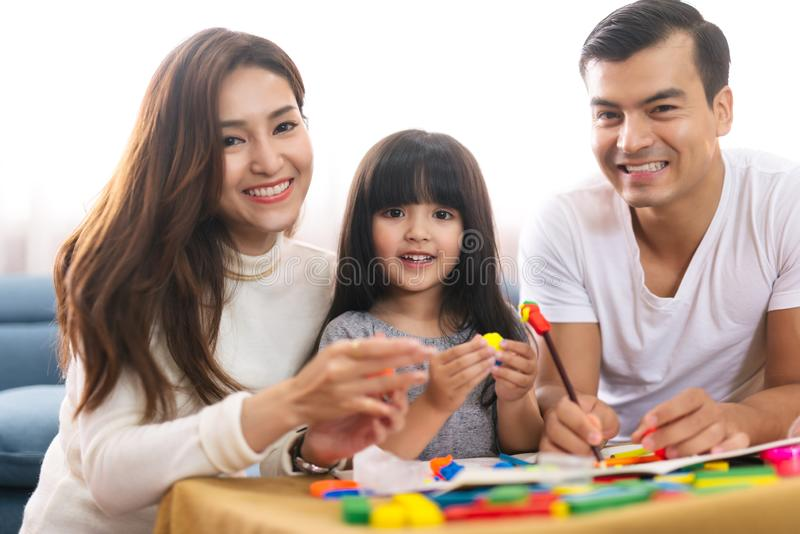 Le portrait de la fille heureuse de fille de famille apprend à employer les blocs colorés de la pâte de jeu jouent ainsi que le p image libre de droits