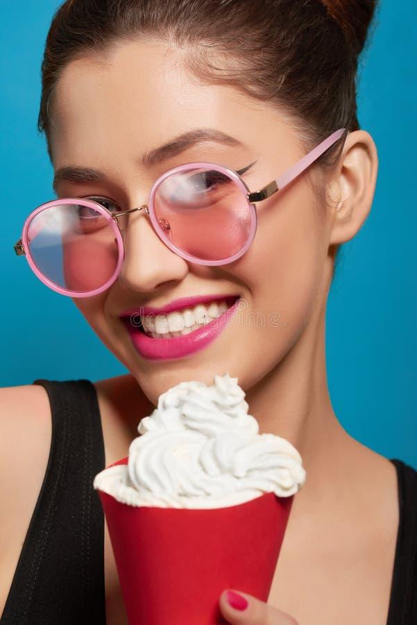 Le portrait de la fille de sourire gardant le rouge peut avec la crème fouettée photos stock