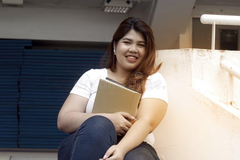 Le portrait de la grosse séance de pose de femme de joli visage souriant asiatique et tiennent un livret photos stock
