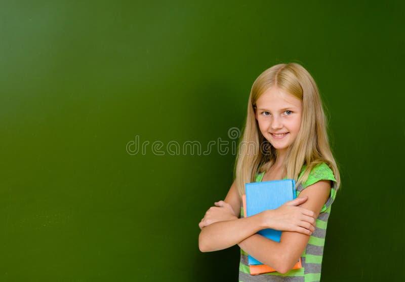 Le portrait de la jeune écolière avec des livres s'approchent du tableau photo stock