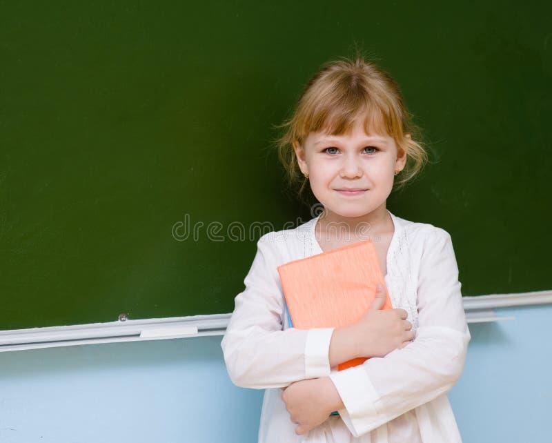 Le portrait de la jeune écolière avec des livres s'approchent du tableau images stock