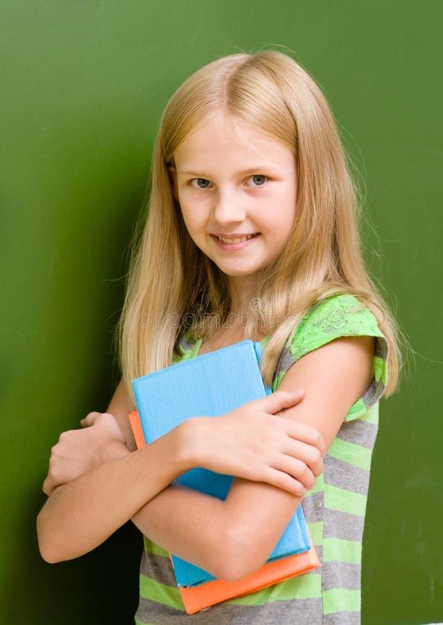 Le portrait de la jeune écolière avec des livres s'approchent du tableau photographie stock libre de droits