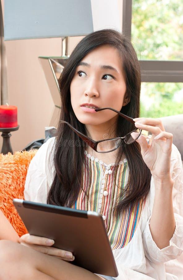 Le portrait de la jeune belle femme étonnante asiatique pense tout en tenant le comprimé images stock