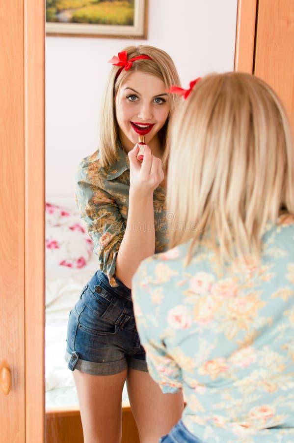Le portrait de la jeune belle femme sexy blonde séduisante ayant la pose d'amusement dessine dans les lèvres rouges de rouge à lè photo stock