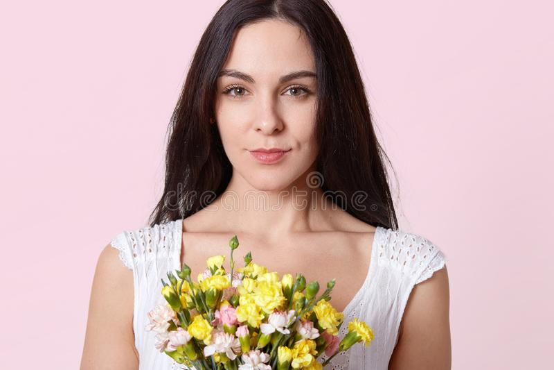 Le portrait de la jeune dame de brune douce, habillé dans la robe blanche, reçoit le cadeau sur l'anniversaire, étant photographi image stock