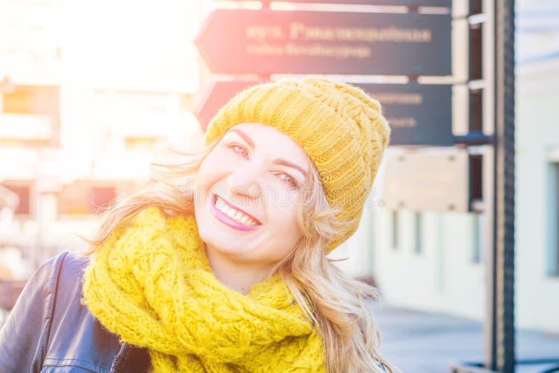 Le portrait de la jeune femme adulte heureuse souriant avec des dents sourient dehors sur les vêtements weating d'hiver de rue d photo stock