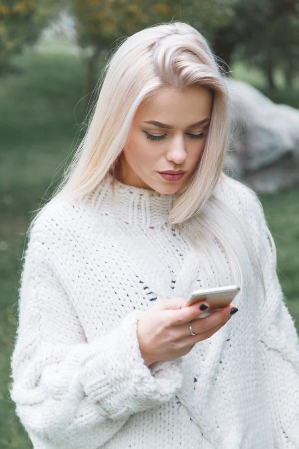 Le portrait de la jeune femme caucasienne de cheveux blonds dans le pull blanc utilise le téléphone extérieur photo stock