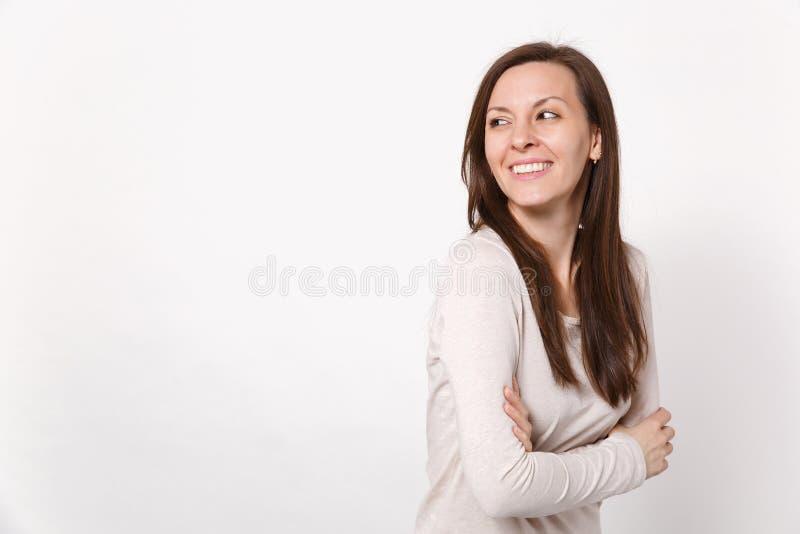 Le portrait de la jeune femme joyeuse gaie dans des vêtements légers regardant de côté tenants des mains s'est plié d'isolement s images stock