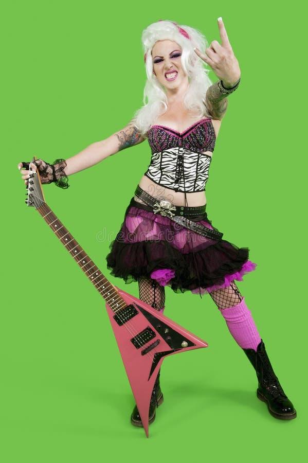 Le portrait de la jeune femme punk tenant la guitare avec la main de roche et de petit pain signent plus de le fond vert photos libres de droits
