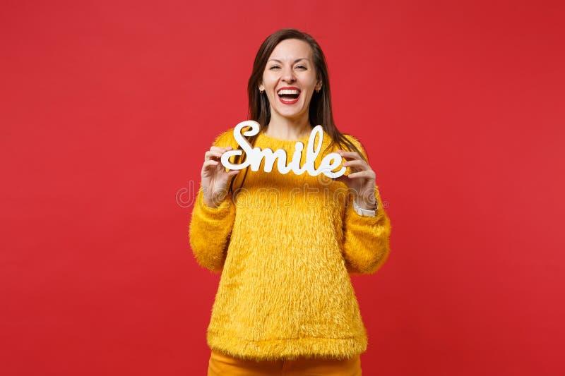 Le portrait de la jeune femme riante dans le chandail jaune de fourrure tenir les lettres en bois de mot sourient d'isolement sur images libres de droits