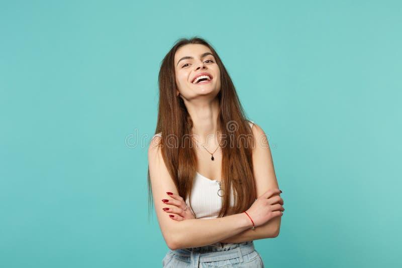 Le portrait de la jeune femme riante dans des vêtements sport légers regardant la caméra tenant des mains a croisé d'isolement su photos libres de droits