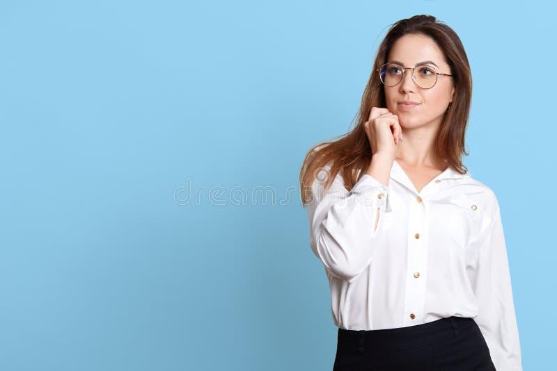 Le portrait de la jeune femme songeuse touchant son menton, a quelque chose à l'esprit, posant avec des expressions du visage réf photos stock