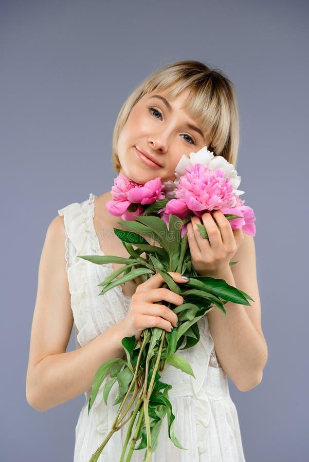 Le portrait de la jeune fille avec le bouquet fleurit au-dessus du backgro gris photographie stock