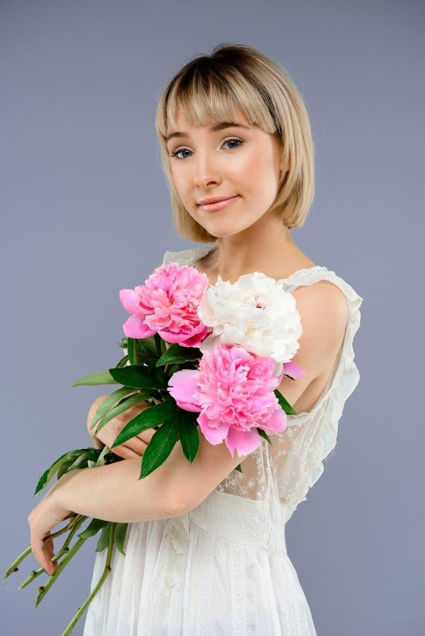 Le portrait de la jeune fille avec le bouquet fleurit au-dessus du backgro gris photos libres de droits