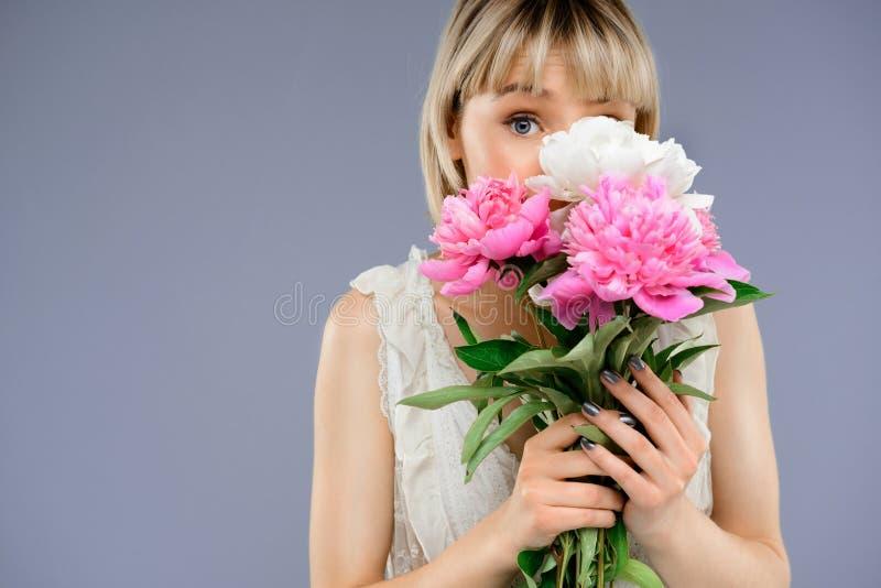 Le portrait de la jeune fille avec le bouquet fleurit au-dessus du backgro gris image stock