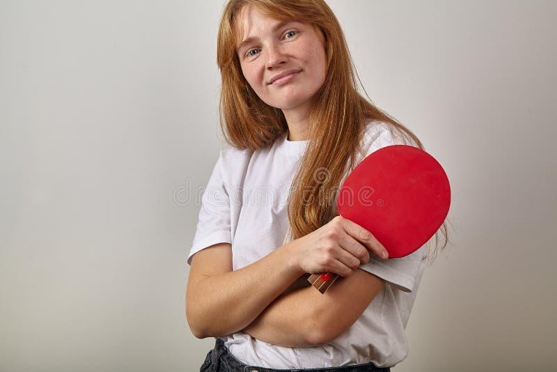 Le portrait de la jeune fille avec les cheveux et les taches de rousseur rouges s'est habillé dans le T-shirt blanc tenant la raq photographie stock libre de droits