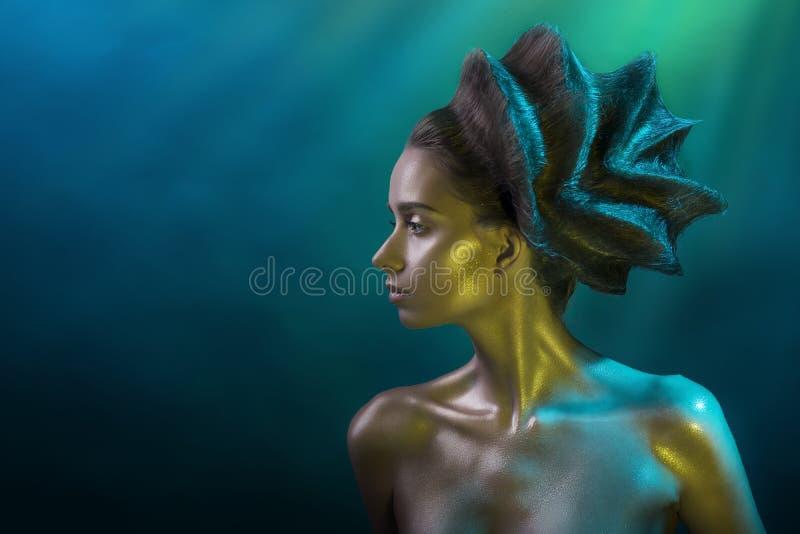 Le portrait de la jeune fille avec une coiffure d'avant-garde et l'éclat préparent dans des tons jaune-bleus sur un fond bleu photo libre de droits