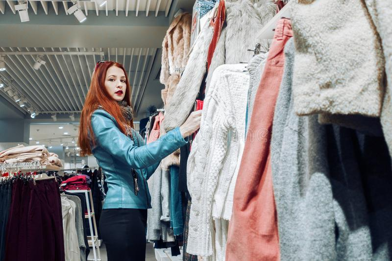 Le portrait de la jeune fille de cheveux rouges dans la femme bleue de veste en cuir shopaholic fait un achat dans le supermarché photo stock