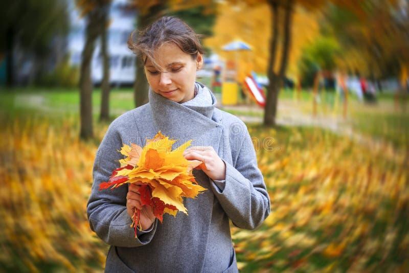 Le portrait de la jeune fille tenant le bouquet du jaune tombé d'automne part dans un parc d'automne avec le bokeh de tourbillonn photos stock