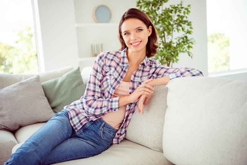 Le portrait de la jeunesse à la mode élégante attrayante gentille de dame reposent le divan sentent l'heureux style bouclé ondule photos stock