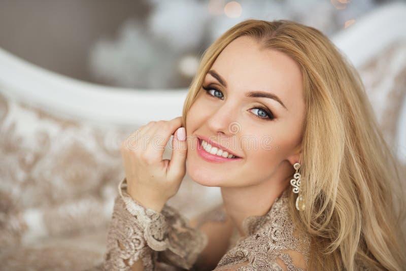 Le portrait de la jolie jeune femme dans la robe de soirée sourit dans Noël photos stock