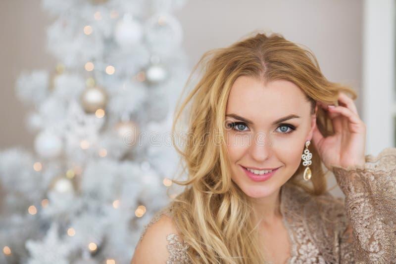 Le portrait de la jolie jeune femme sourit et touche ses longs cheveux photos stock