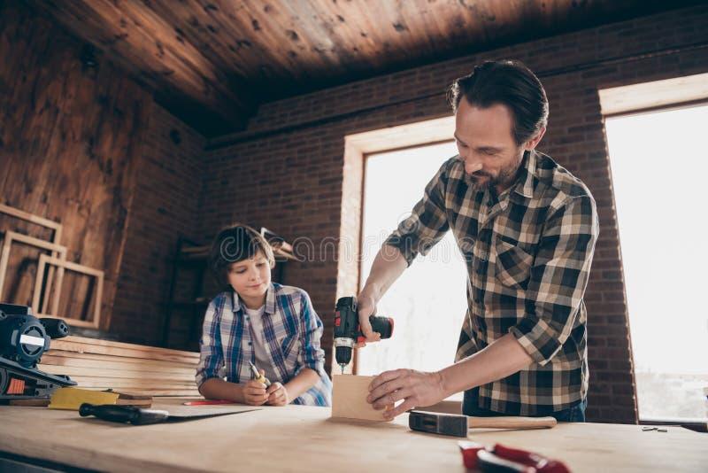 Le portrait de la jolie main focalisée intéressante avec du charme de prise de père de fils font mettre à des artisans d'équipeme images libres de droits