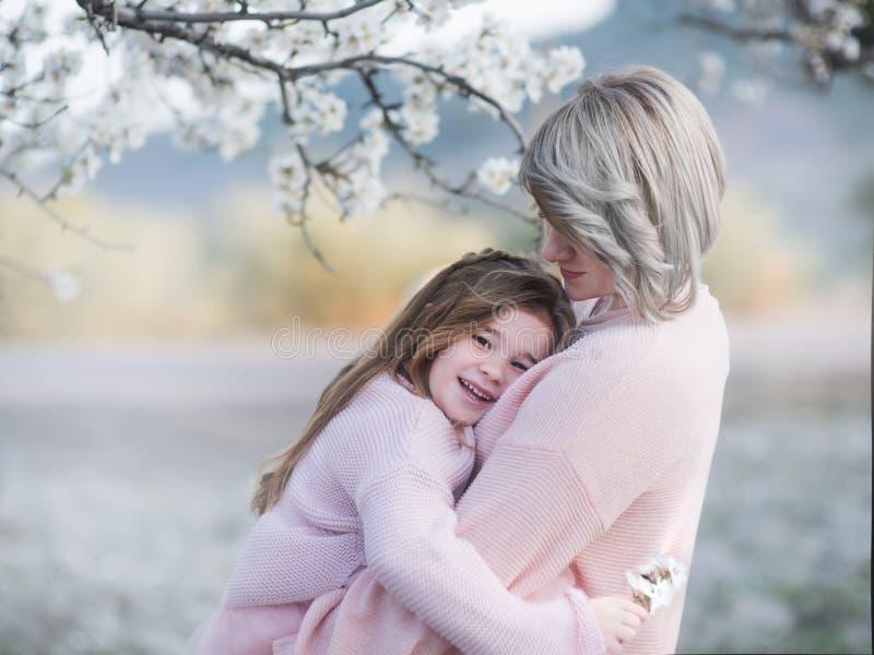 Le portrait de la mère et la fille embrassent doucement dans le jardin avec l'almendra fleurissant photo libre de droits