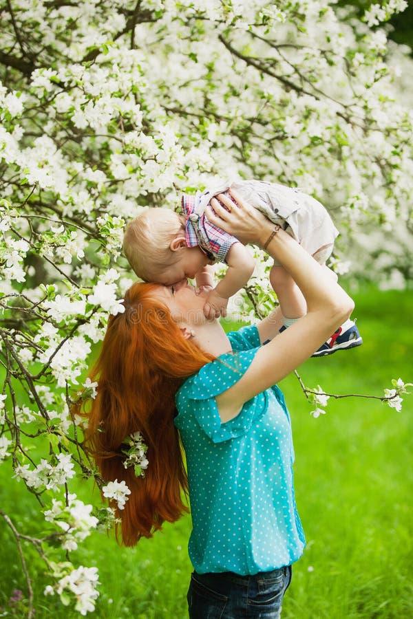 Le portrait de la mère heureuse heureuse et le fils font du jardinage au printemps photos stock