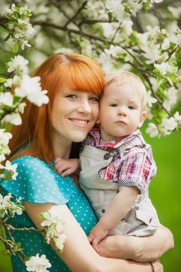 Le portrait de la mère heureuse heureuse et le fils font du jardinage au printemps photo stock