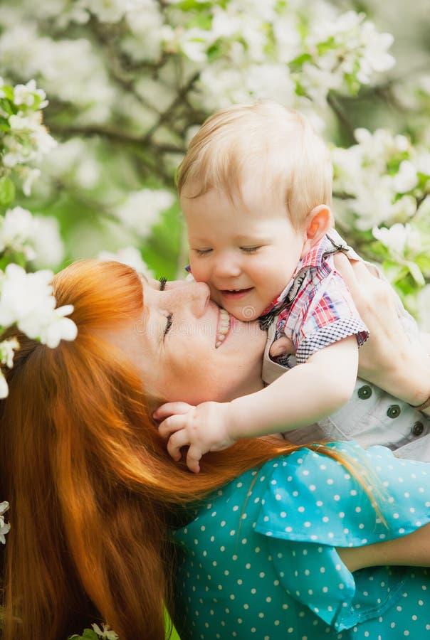 Le portrait de la mère heureuse heureuse et le fils font du jardinage au printemps photos libres de droits