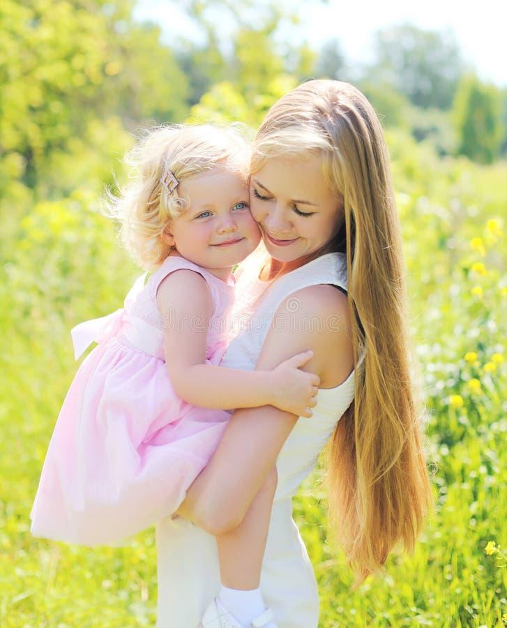 Le portrait de la mère se tenant dessus remet l'enfant étreignant en été images stock